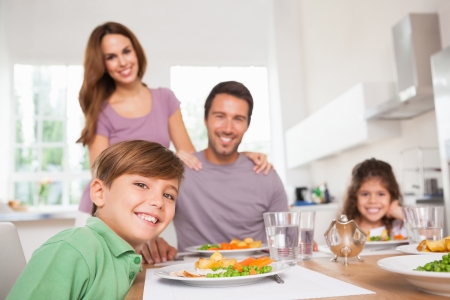 standing water: Family looking at the camera at dinner time in kitchen