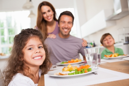multiracial family: Family smiling at the camera at dinner table in kitchen
