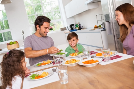 multiracial family: Father serving vegetables to son in kitchen