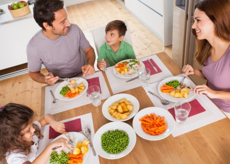 children eating: Family smiling around a healthy meal in kitchen