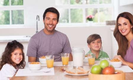 Family having breakfast in kitchen photo