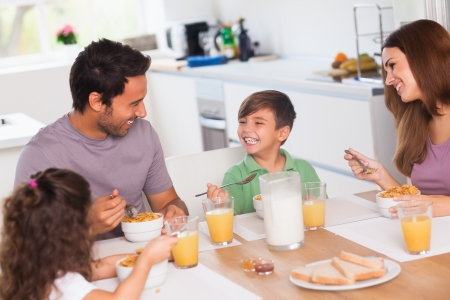 Family laughing around breakfast in kitchen