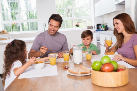 comiendo cereal: Familia comiendo desayuno saludable en la cocina