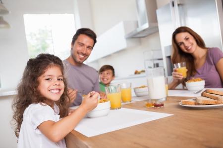 familia comiendo: Familia sonriendo a la cámara en el desayuno en la cocina