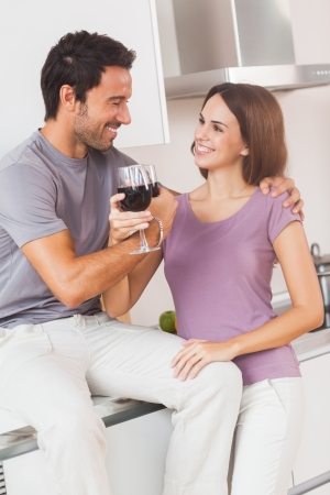 Couple toasting with arms crossed with a glass of wine in kitchen photo