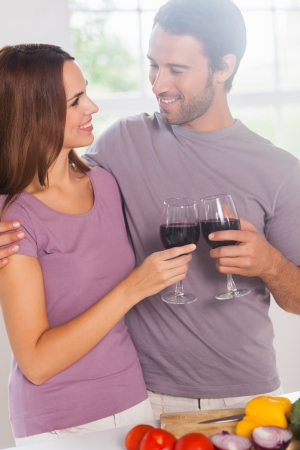 Lovers toasting standing with a glass of wine in kitchen photo