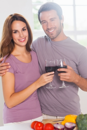 Lovers toasting with a glass of wine and looking camera in kitchen photo
