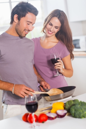 Couple preparing food and drinking in kitchen photo