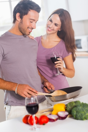 Lovers preparing food and drinking in kitchen photo