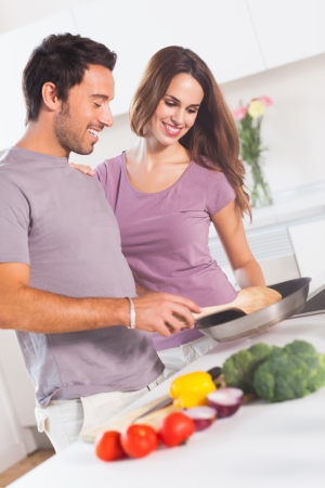Couple preparing food at the stove in kitchen photo