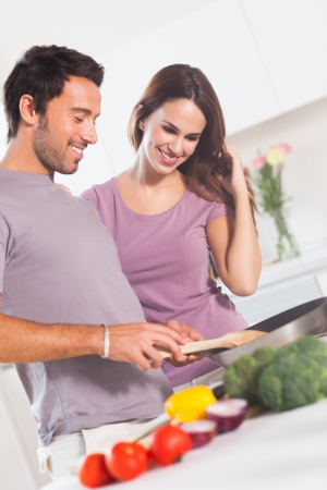 Happy couple making dinner in kitchen photo