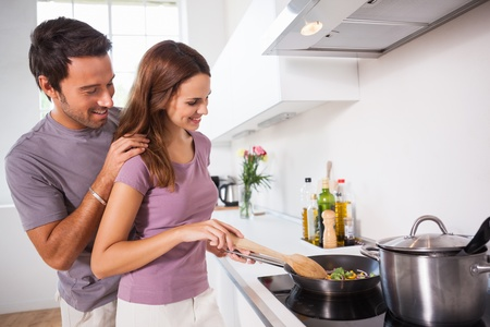 Woman making dinner with partner watching in kitchen photo