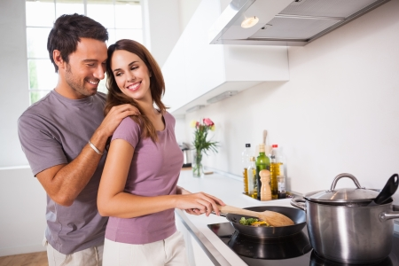 Woman preparing food at the stove with partner behind her in kitchen photo