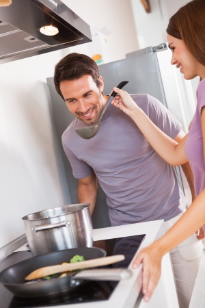 Woman getting man to taste dinner in kitchen photo