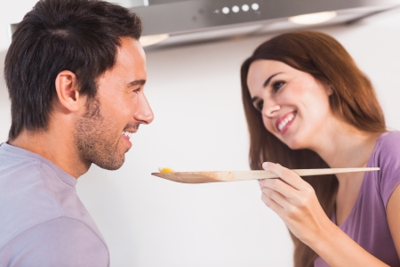 Man tasting dish on wooden spoon in kitchen photo