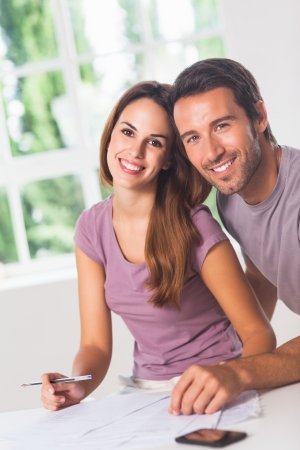 Couple smiling at the camera with invoices and phone photo
