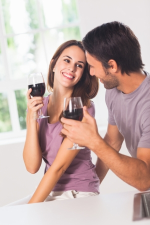 Smiling couple with wine in house photo