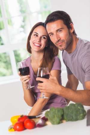 Smiling couple with wine and vegetables in kitchen Stock Photo - 18122481