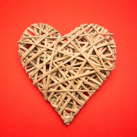 Wicker heart on red background photo