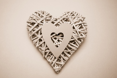 paper cut out: Wicker heart ornament with paper cut out on grey background Stock Photo