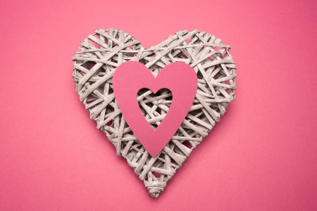 paper cut out: Wicker heart ornament with paper cut out on pink background