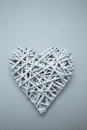 Wicker heart on blue background photo