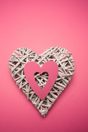 paper cut out: Wicker heart ornament with pink paper cut out on pink background