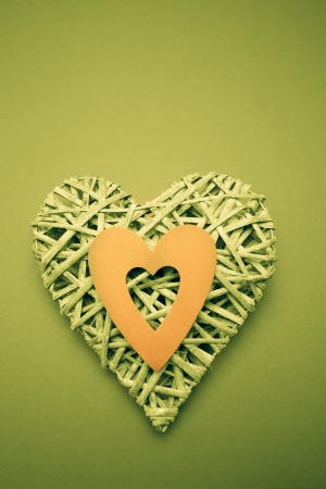 paper cut out: Wicker heart ornament with green paper cut out on green background