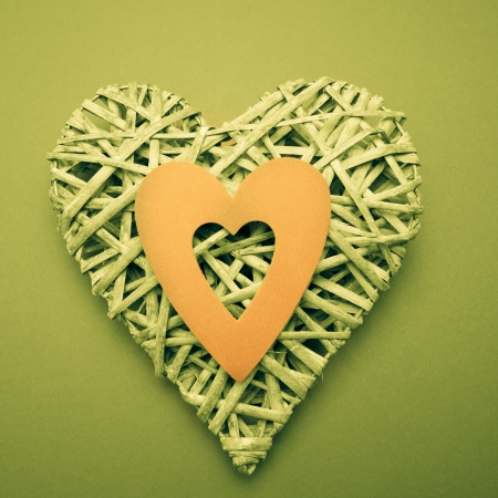 paper cut out: Wicker heart ornament with yellow paper cut out on green background Stock Photo