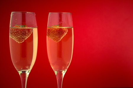 Two glasses of champagne with strawberries on red background photo