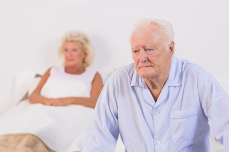 afflict: Unsmiling old couple in the bedroom Stock Photo