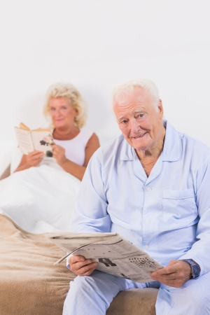 Old persons looking at camera while reading on the bed photo