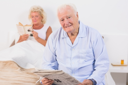Aged couple looking at camera while reading in the bedroom photo