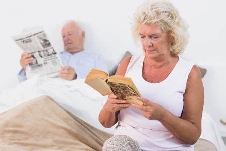 Aged couple reading a book and newspaper on the bed Stock Photo - 18125665