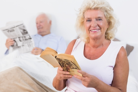 Smiling old couple reading book and newspaper in the bedroom photo
