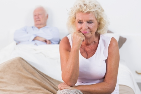Discouraged old woman sitting on the bed with old man sleeping photo