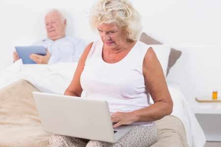 Aged couple using a tablet and the laptop in the bedroom photo