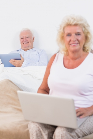Happy old couple using a tablet and the laptop in the bedroom photo