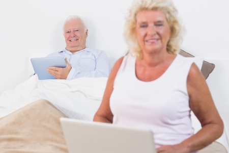 Smiling old couple using a tablet and the laptop in the bedroom photo