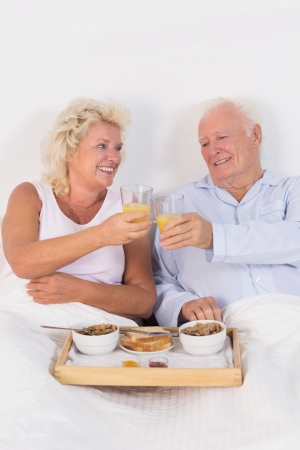 Old couple toasting at breakfast with orange juice and lying on the bed photo