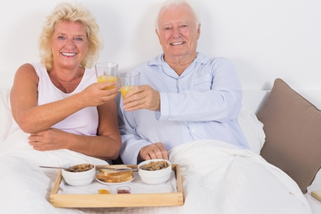 Smiling aged couple toasting and lying on the bed photo