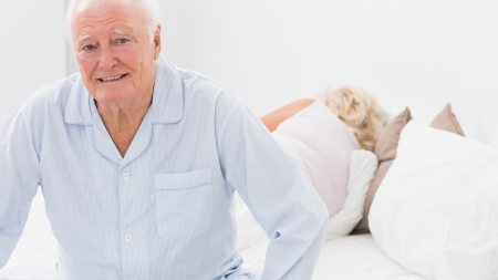 Old man sitting while woman sleeping on the bed photo