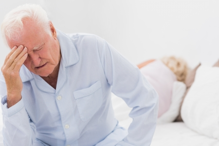 Old man suffering while woman sleeping on the bed photo