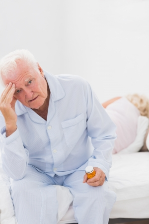 Elderly man suffering while woman sleeping on the bed photo