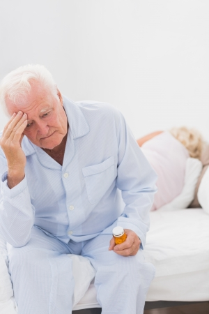 Old man having a headache while woman sleeping on the bed photo