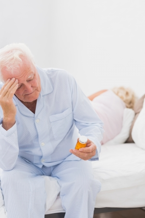 Old man holding pills while woman sleeping on the bed photo