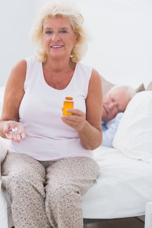 sleeping tablets: Old woman with an opened pill bottle with a man sleeping on the bed Stock Photo