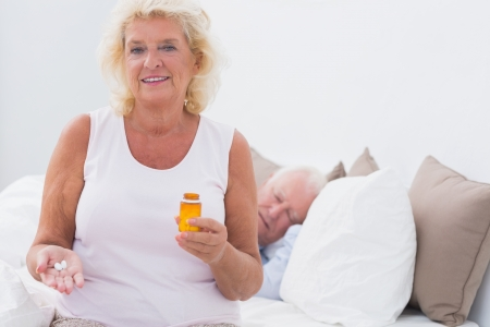 Old woman with the opened pill bottle with a man sleeping on the bed photo