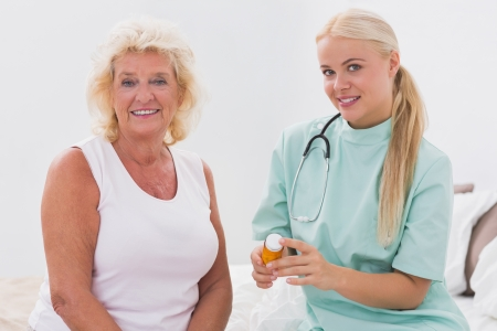 giver: Home nurse and patient posing in bedroom Stock Photo
