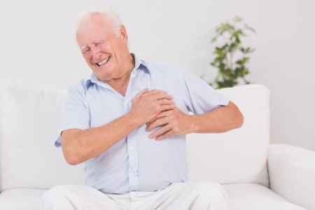 heart pain: Old man suffering with heart pain on a sofa
